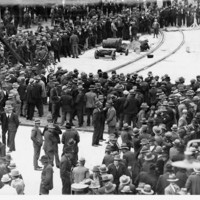 Image: A large group of men wearing suits and hats congregate near a train line