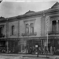 Image: a black and white photograph of a two storey terrace building with large plate glass shop windows on the first floor displaying a range of clothing and fabrics