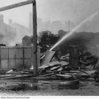 Image: A jet of water is directed at a large, smouldering pile of debris. Burned-out buildings are visible in the background through a haze of smoke