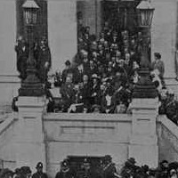 Image: a large crowd swarms the pavement in front of a twin curved staircase which leads up to a stone building with columns.