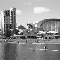 Image: rowers travel down a wide river with grassy banks in front of a 24 storey skyscraper and a large convention centre with a multi-storey curved glass wall.