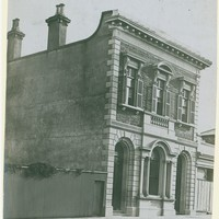 Image: two story building with large arched windows at front