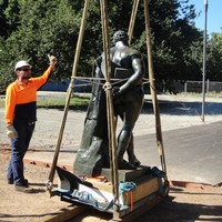 Image: man in hard hat and hi-vis supervising statue being lifted using hoist