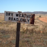 Image: Outback landscape and road with sign, stating 'Dry weather road only'