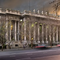 Image: A large stone building with two storey high columns lining its front is lit up by green lights at dusk.