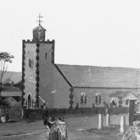 Image: a black and white copy of a watercolour painting which shows men, women and children in 1840s dress walking or riding in horse drawn carts towards a simple stone church with a single tower which is surrounded by cottages.