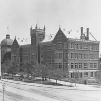 Image: A large, five storey, brick and stone building with a central tower, bay windows, crenellated parapet and pitched iron roof. The dome of the exhibition building can be seen behind.