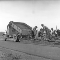 Image: Black and white photo of a drag box being used to spread hotmix (bituminous concrete), this method was a cheap way to provide a smooth surface, 10 November 1937.