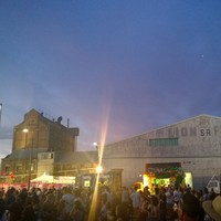 Image: crowd of people in front of stage and buildings