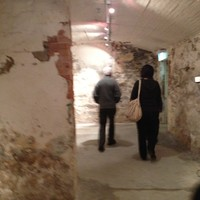 Image: two people walking through underground brick-walled rooms