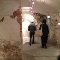 Image: two people walking through underground brick-walled rooms