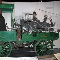 Image: A green automobile with a steam engine and spoked wagon wheels on display in a museum