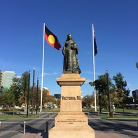 Image: large statue of woman with two flags behind