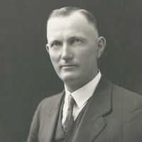 Image: Upper body portrait photograph of a man wearing a suit