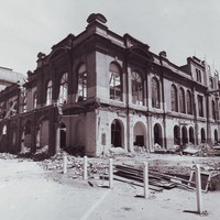 Image: An exterior view of a large building in the process of being demolished. The roof has been taken off, glass has been removed from the windows and all the interior walls have been knocked down.