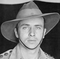 Image: An upper body portrait photograph of a man in an army uniform, and wearing an army hat with chin strap.