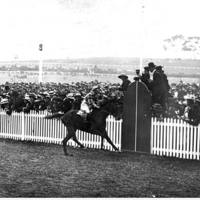 Image: Black and white photo of horseracing in progress, crowd behind a fence
