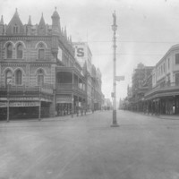 Image: a wide intersection with a lamppost in the centre. On one corner is an ornate three storey building with a verandah, balcony and highly decorative and detailed parapet.