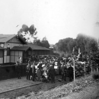Image: group of people with flags gathered in front of building on railway tracks