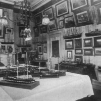 Image: A small room festooned with several works of art on its walls and ship models on tables