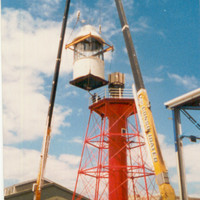 Image: A large crane hoists the lantern room of a pre-fabricated metal lighthouse to the top of the lighthouse tower. The lantern room is white and the lighthouse tower is red. A warehouse is visible in the background