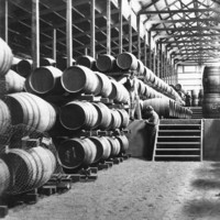 Image: Two men working in large shed space with wine barrels