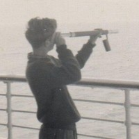 Image: boy holding telescope and looking out over ocean