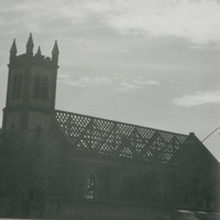 Image: a church with roof tiles removed.