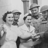 Image: Two women in white dresses hand cigarettes to a group of five men in military uniforms and helmets