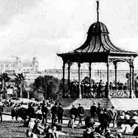 Image: A crowd of people in early twentieth century attire sit on the grass around a rotunda where a band plays