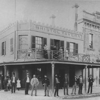 Image: group stand in front of a tavern building with four women standing on a balcony in the tavern