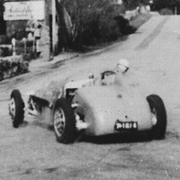Image: A 1950s vintage racing car drives around a corner and through the streets of a small rural town. A handful of small historic stone buildings are visible on either side of the road