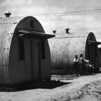 Image: children playing in dirt ditch in front of row of curved tin buildings