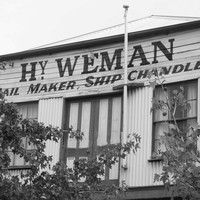 Image: The upper floor of a rectangular building with two windows and a set of double-doors. The words 'Hy. Weman. Sail Maker, Ship Chandler' are painted on the building front
