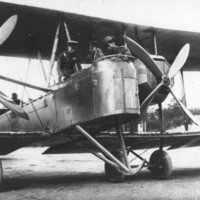 Image: bi-plane on ground with men in cockpit and standing on lower wing
