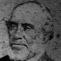 Image: A faded head-and-shoulders photographic portrait of an elderly man with thinning hair and a chin-beard