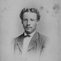 Image: Photographic portrait of a man with wispy stubble and short slightly curly hair. He is wearing a suit jacket, shirt and small bow tie.