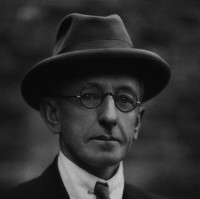 Image: black and white photo of man in glasses, hat and suit