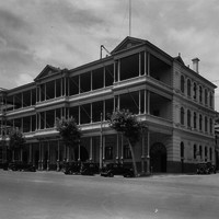 Image: three storied building with large, front facing balcony