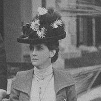 Image: women in dress with hat sitting down next to man in suit and top hat