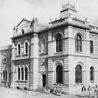 Image: An imposing, two-storey stone building in Victorian-Italianate style stands at the intersection of two dirt streets. A small group of men and boys stand in front of the building