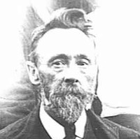 Image: A photographic head-and-shoulders portrait of a middle-aged man with a goatee and full head of hair. He is wearing an Edwardian-era suit and tie
