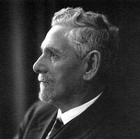 Image: A photographic head-and-shoulders portrait of a white-haired man with goatee. He is wearing a suit and is standing with his arms crossed
