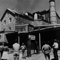 Sepia photo of group of people in front of an old stone mill building