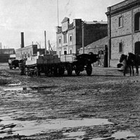 Image: Horse and cart and pedestrians on muddy unpaved roadway with stone and brick buildings either side