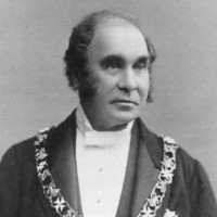Image: Black and white photograph of man wearing formal clothes and livery collar