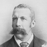 Image: A photographic head-and-shoulders portrait of a young Caucasian man wearing a late-Victorian era suit and sporting a very large handlebar moustache