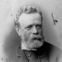 Image: A photographic head-and-shoulders portrait of a bearded, middle-aged man wearing a suit with cravat and jewelled cravat pin