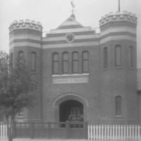 Image: A large, two-storey brick building built in mock-Tudor style, with two turrets flanking a large entrance door. A sign reading 'Missions to Seamen' is visible above the entrance door
