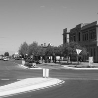 A large wide street in foreground extends into the distance. There is a large white stone building on the right hand corner